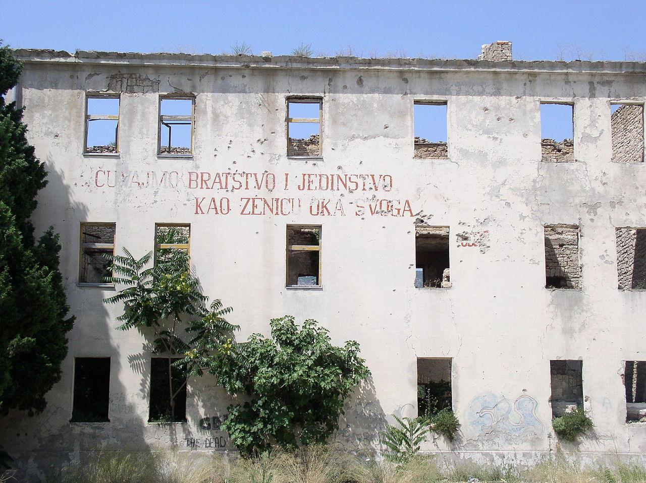 """Natpis """"Čuvajmo bratstvo i jedinstvo"""" na zgradi u Mostaru srušenoj tokom građanskog rata (Foto: Wikimedia/Antidiskriminator)"""