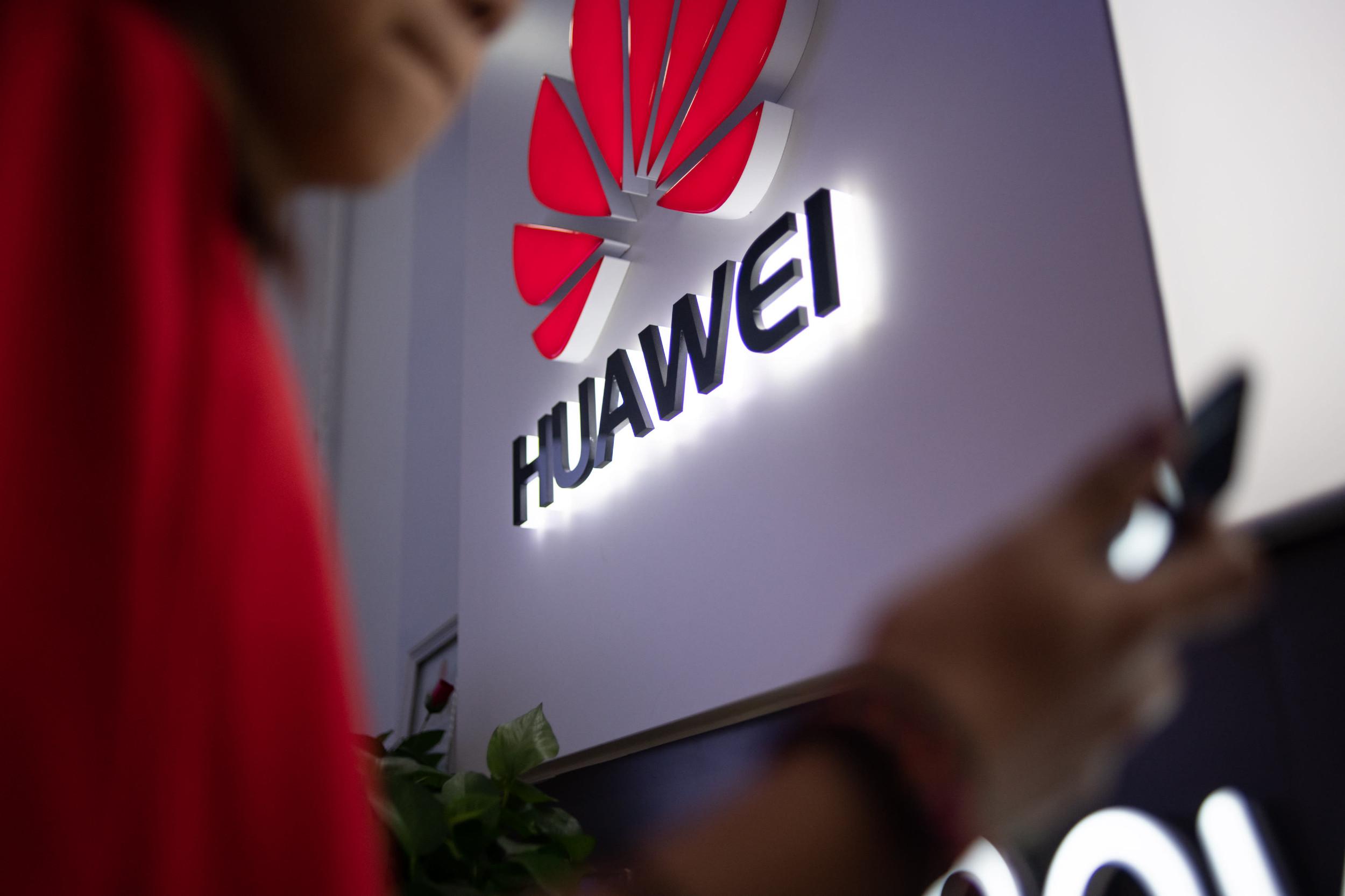 Човек гледа у свој телефон док пролази поред продавнице Хуавеја у Пекингу, 27. мај 2019. (Фото: Fred Dufour/AFP/Getty Images)