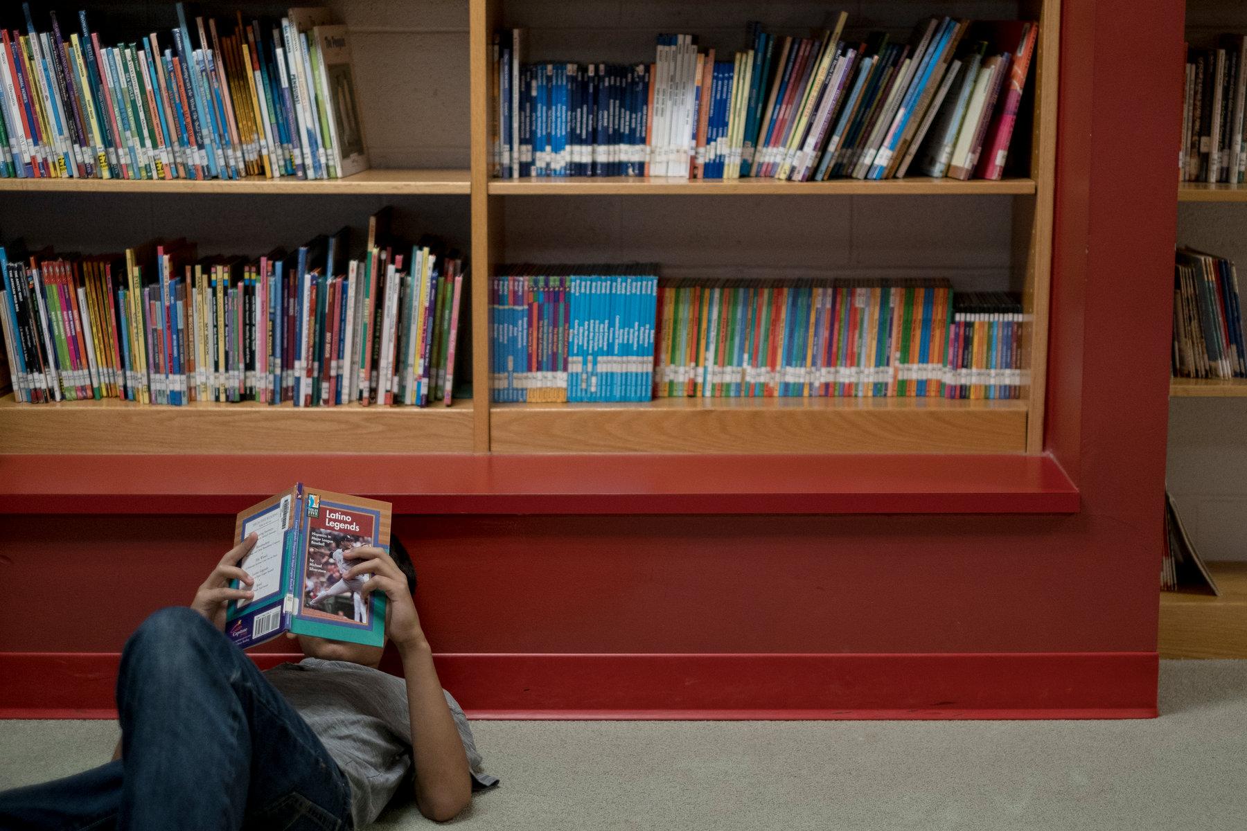 Студент чита књигу у библиотеци у једној школи у Балтимору (Фото: Gabriella Demczuk/The New York Times)