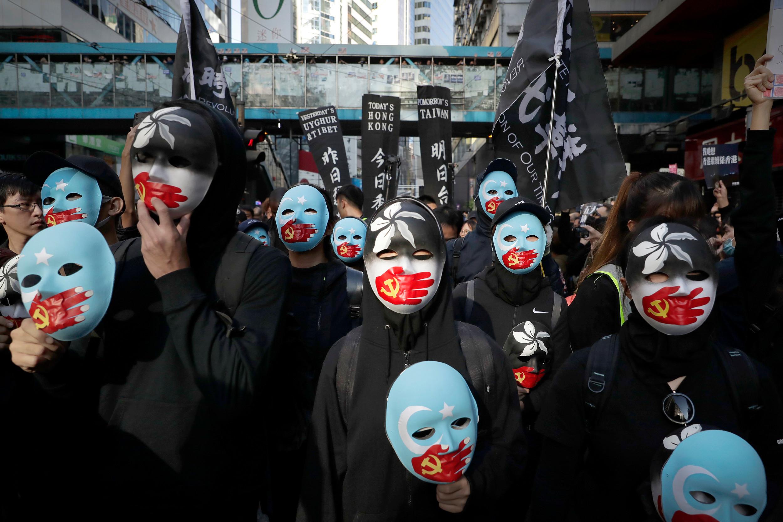 Демонстранти у Хонгконгу носе маске са заставама Хонгконга у црној варијанти и тзв. Источног Туркестана преко којих се налази рука с грбом Комунистичке партије Кине која покрива уста, 08. децембар 2019. (Фото: AP Photo/Mark Schiefelbein)
