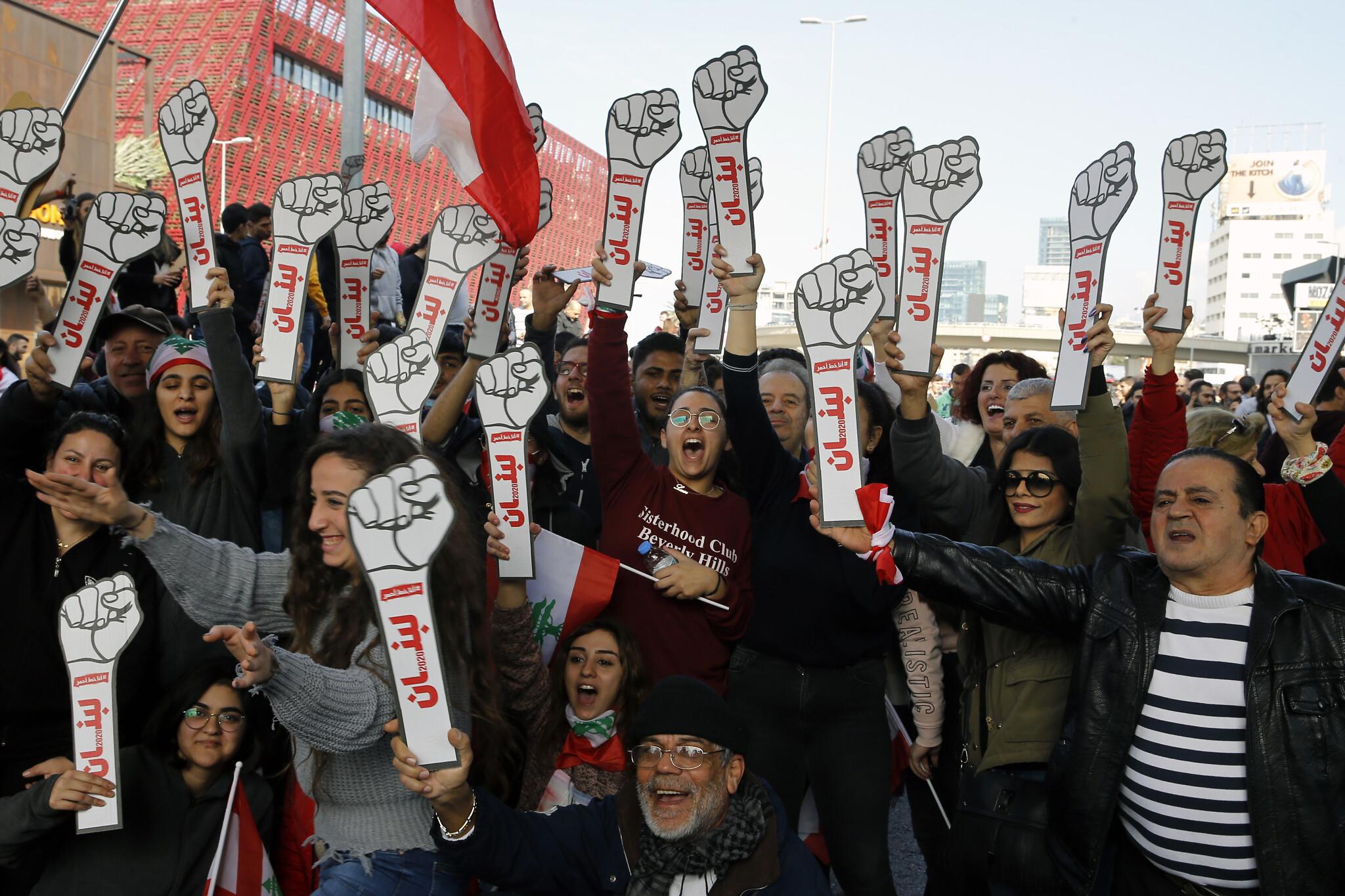 """Demonstranti drže kartonske stisnute pesnice na kojima na arapskom piše """"revolucija"""", Bejrut, 14. januar 2020. (Foto: AP Photo/Bilal Hussein)"""