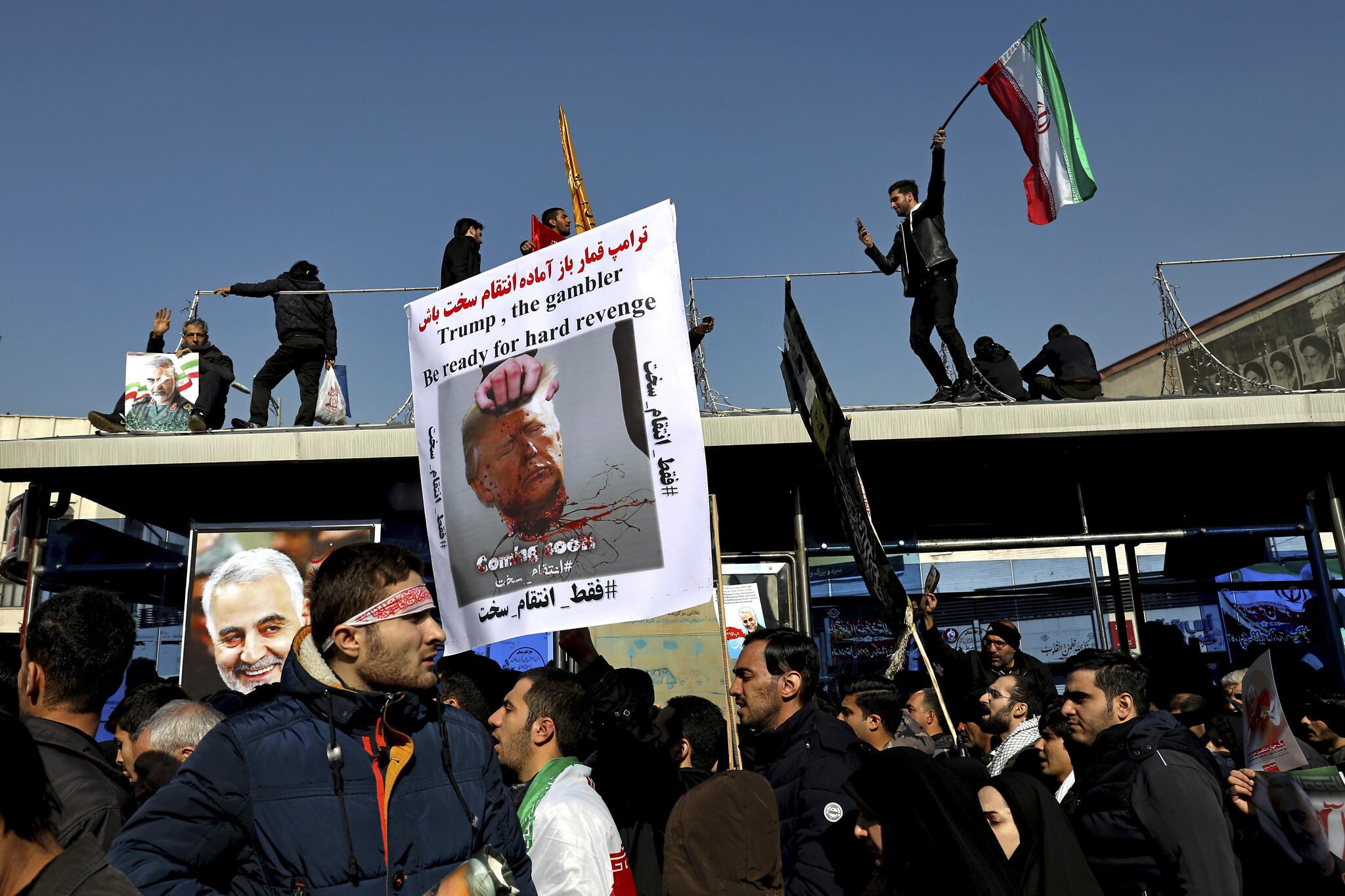 Iranci mašu zastavama i drže sliku obezglavljenog Donalda Trampa, Teheran, 06. januar 2020. (Foto: Ebrahim Noroozi/AP)