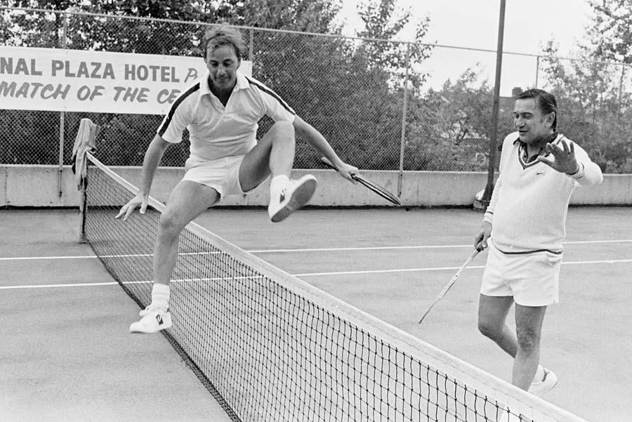 Премијер Британске Колумбије Бил Бенет прескаче мрежу током тениског меча са градоначелником Ванкувера Џеком Волричом, Ванкувер, јун 1978.