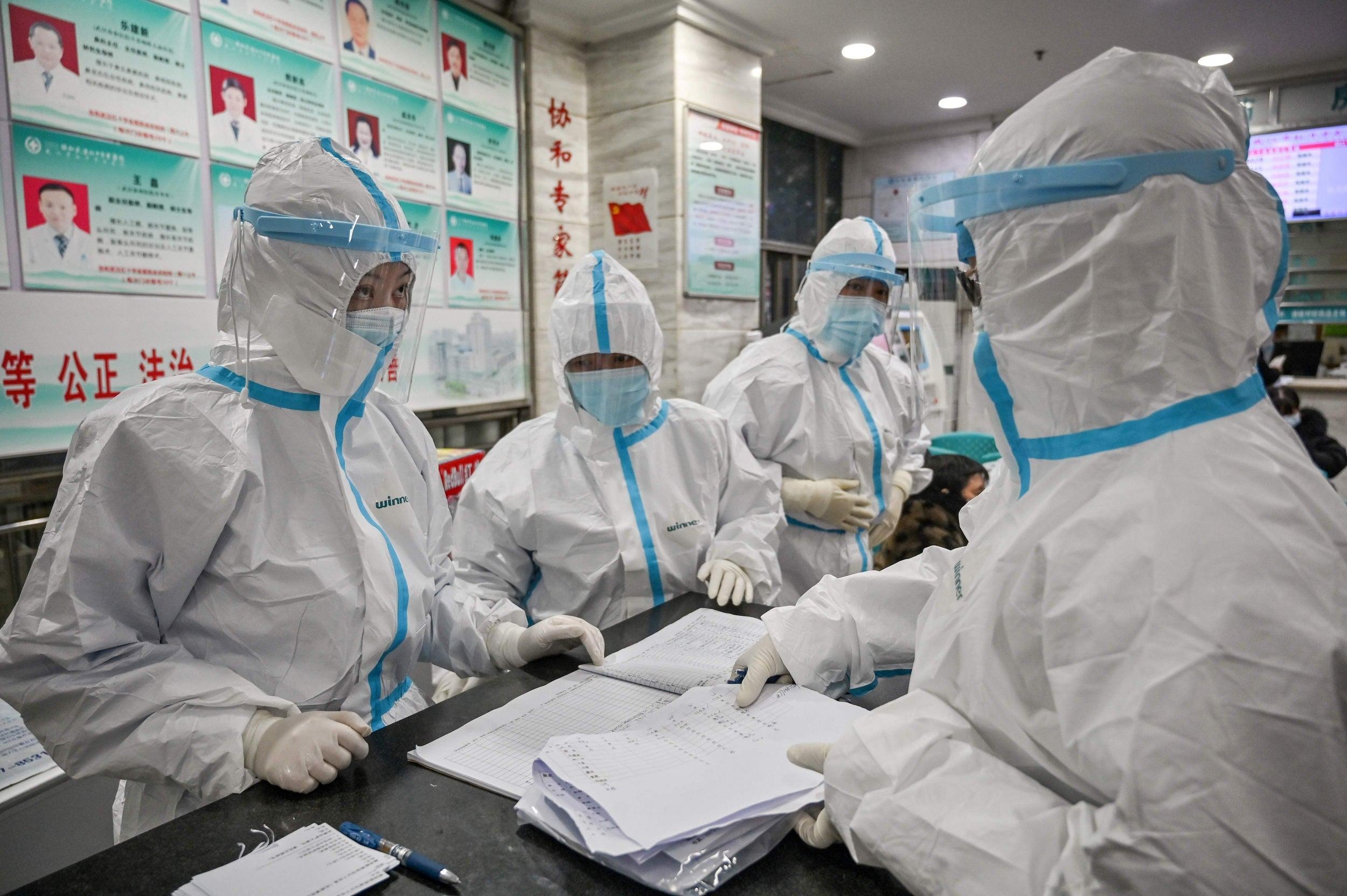 Članovi medicinskog osoblja u zaštitnim odelima razgovaraju u bolnici Crvenog krsta, Vuhan, 25. januar 2020. (Foto: Hector Retamal/Agence France-Presse/Getty Images)
