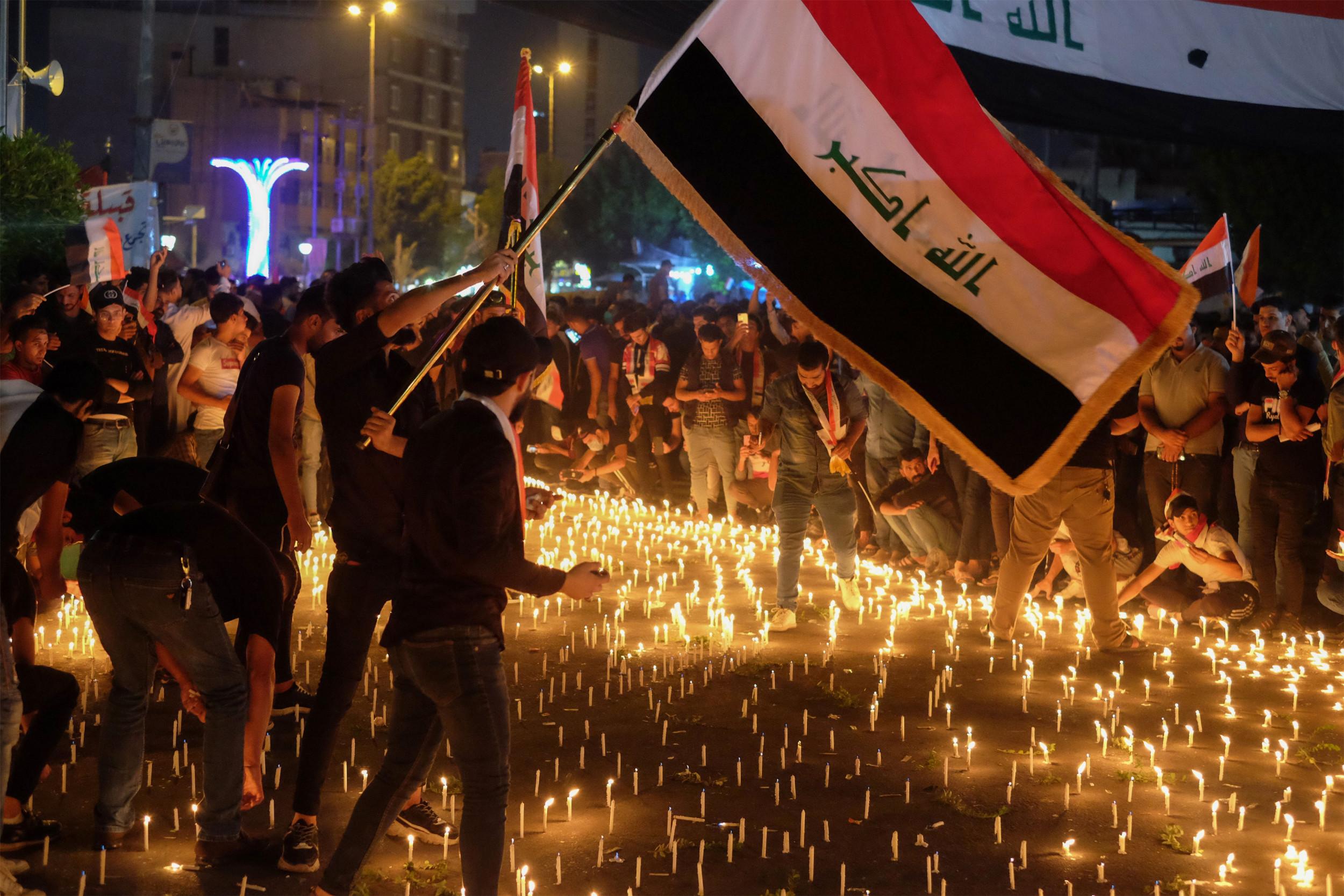 Demonstranti mašu zastavom Iraka i pale sveće za ubijene ljude tokom protesta, Bagdad, 01. novembar 2019. (Foto: MOHAMMED SAWAF/AFP via Getty Image)