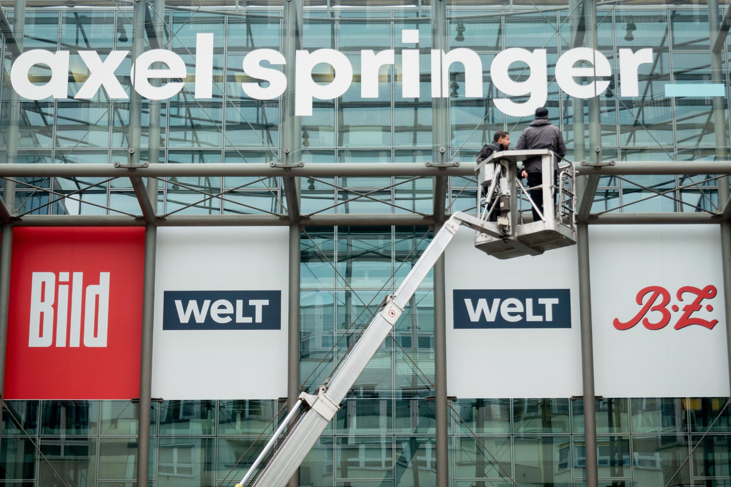 Radnici nameštaju banere na upravnoj zgradi kompanije Aksel Špringer u Berlinu (Foto: Kay Nietfeld/Getty Images)