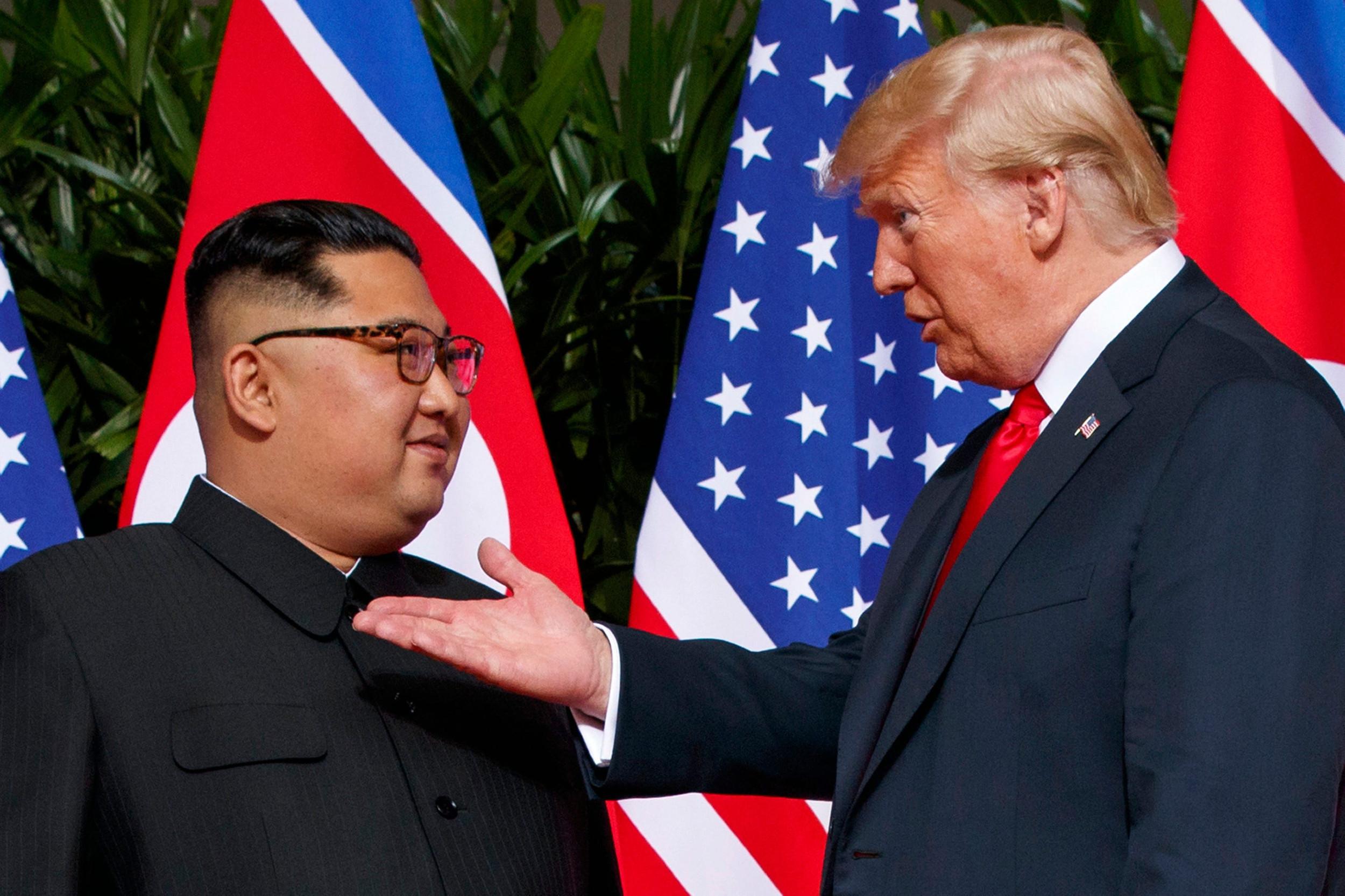 Амерички председник Доналд Трамп разговара са лидером Северне Кореје Ким Џон Уном током њиховог првог састанка у Сингапуру, 12. јун 2018. (Фото: AP Photo/Evan Vucci)