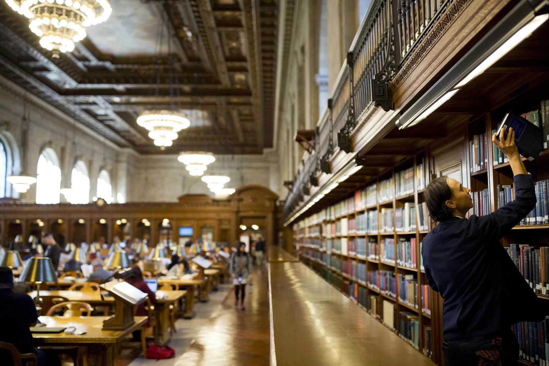 Човек узима књигу са полице у Њујоршкој јавној библиотеци (Фото: AFP)