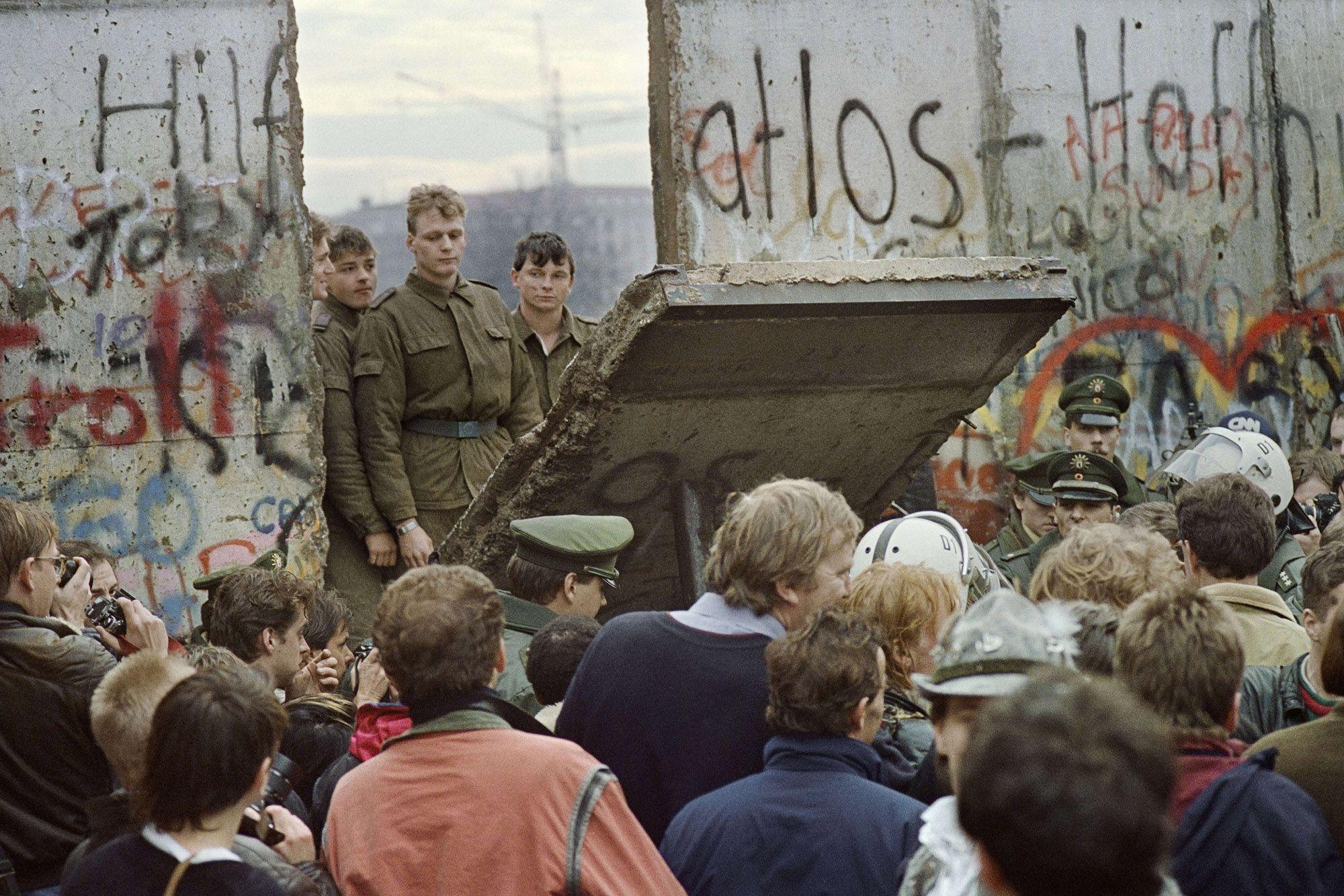 Окупљени људи из западног дела Берлина посматрају како војници из источног дела руше један део Берлинског зида, 11. новембар 1989. (Фото: GERARD MALIE/AFP/Getty Images)