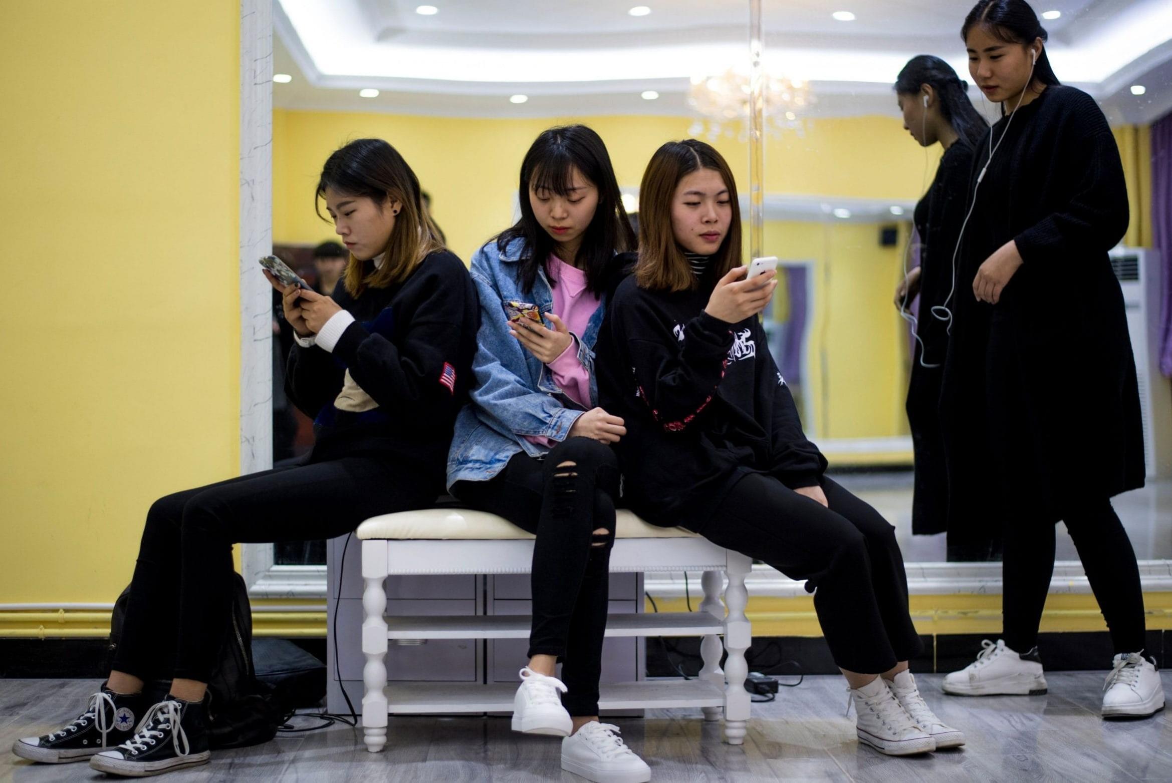 Mlade Kineskinje zamišljeno gledaju u pametne telefone (Foto: Johannes Eisele/AFP)