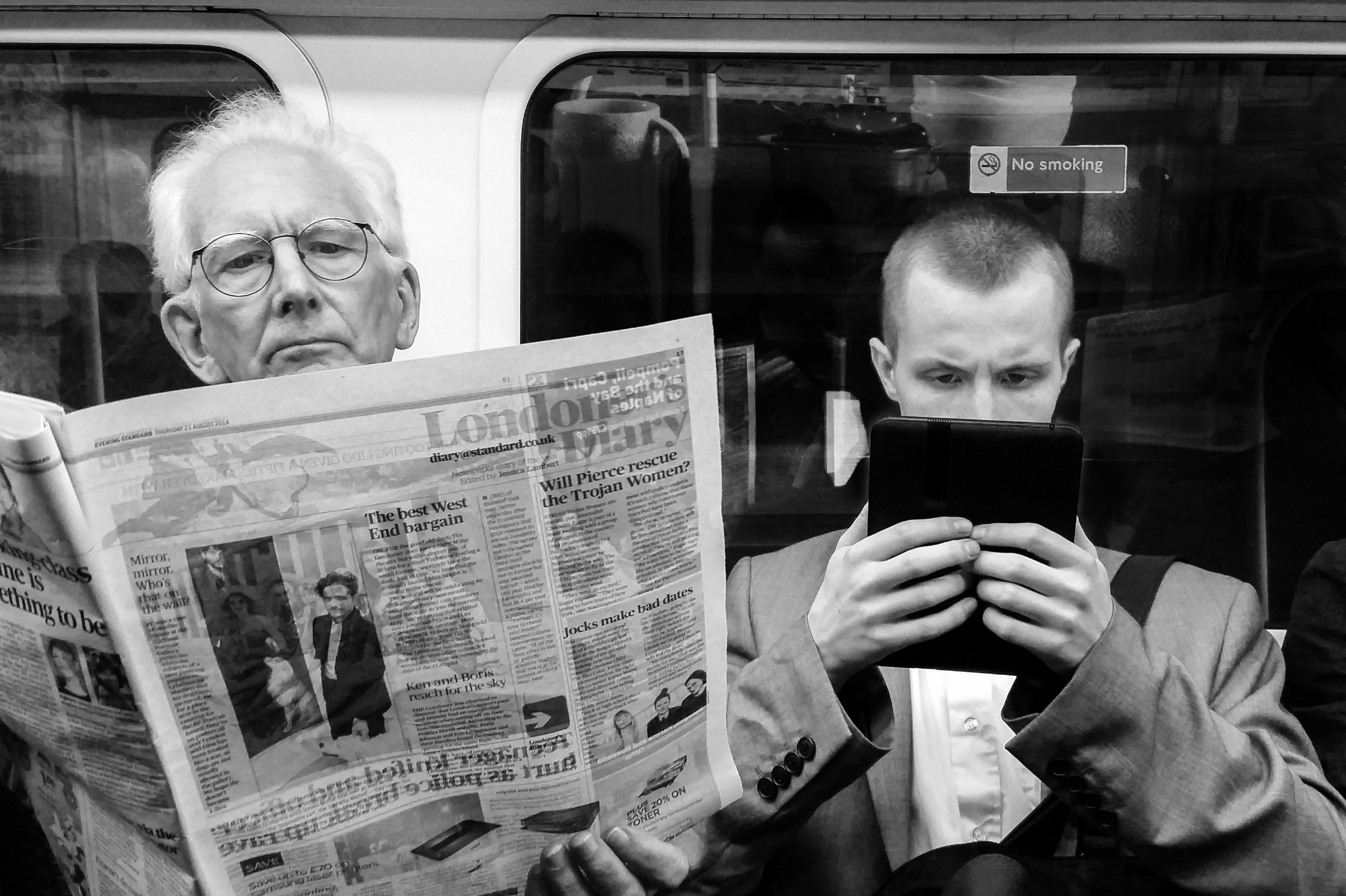 Сцена из лондонског метроа у којој старији човек чита дневне новине, а млађи чита вести на таблету (Фото: Flickr/Matthew G)