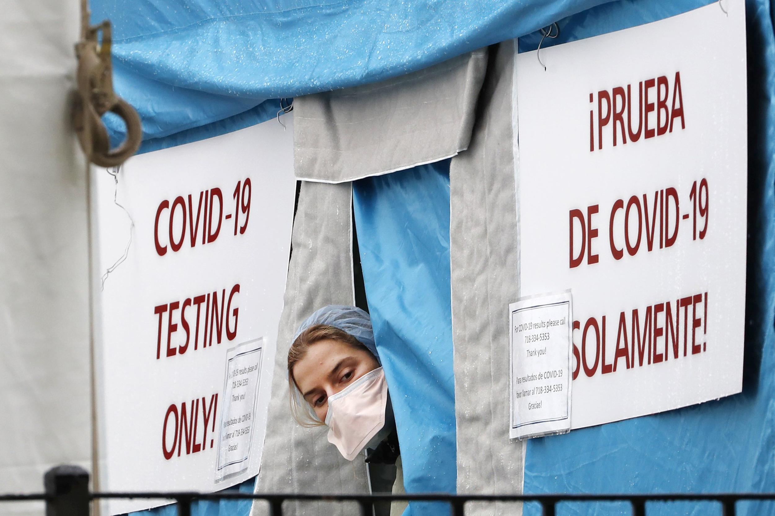 Медицинска радница гледа кроз шатор постављен испред једне од њујоршких болница за тестирање на COVID-19, 28. март 2020. (Фото: AP Photo/Kathy Willens)