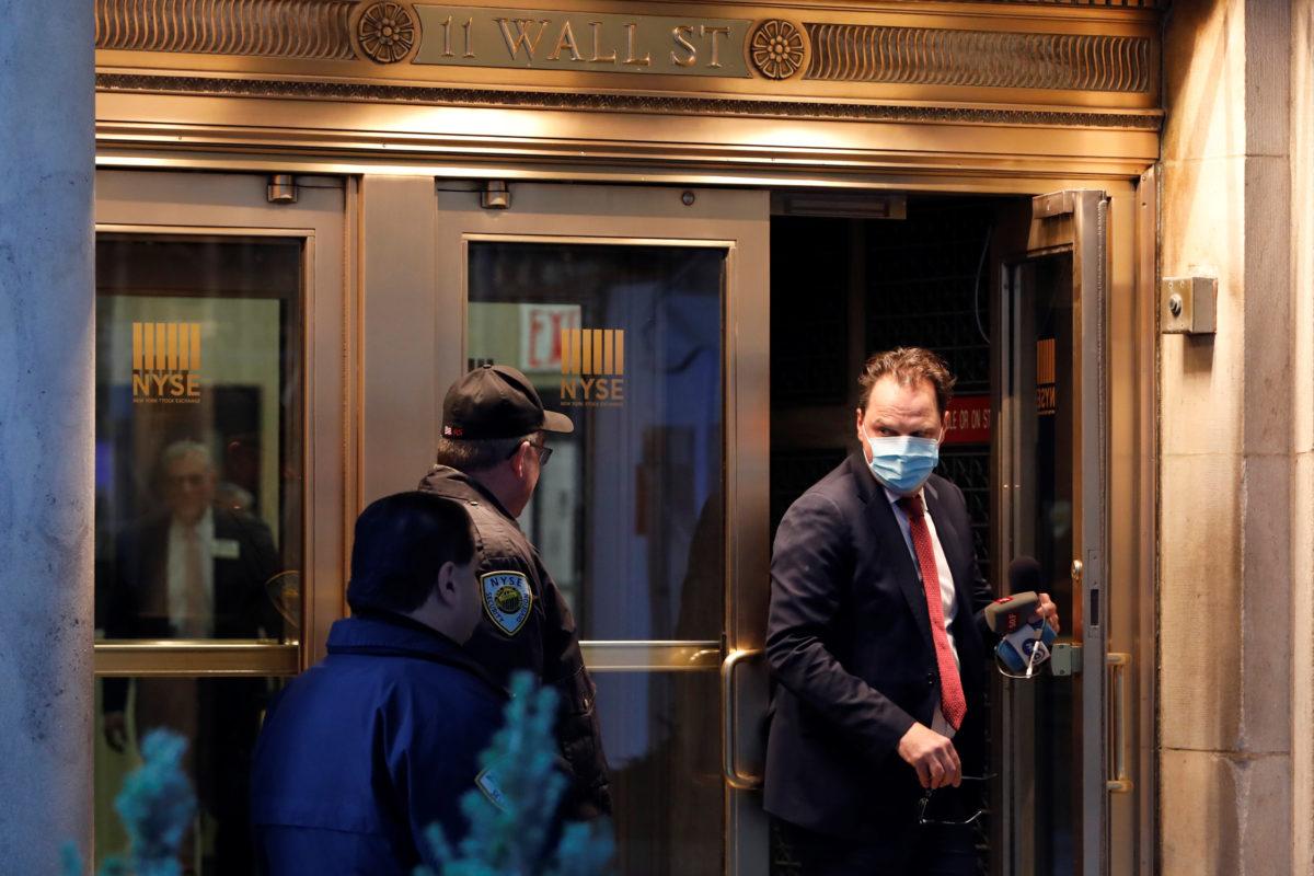 Човек са хируршком маском на лицу излзи из Њујоршке берзе, 16. март 2020. (Фото: REUTERS/Stringer)