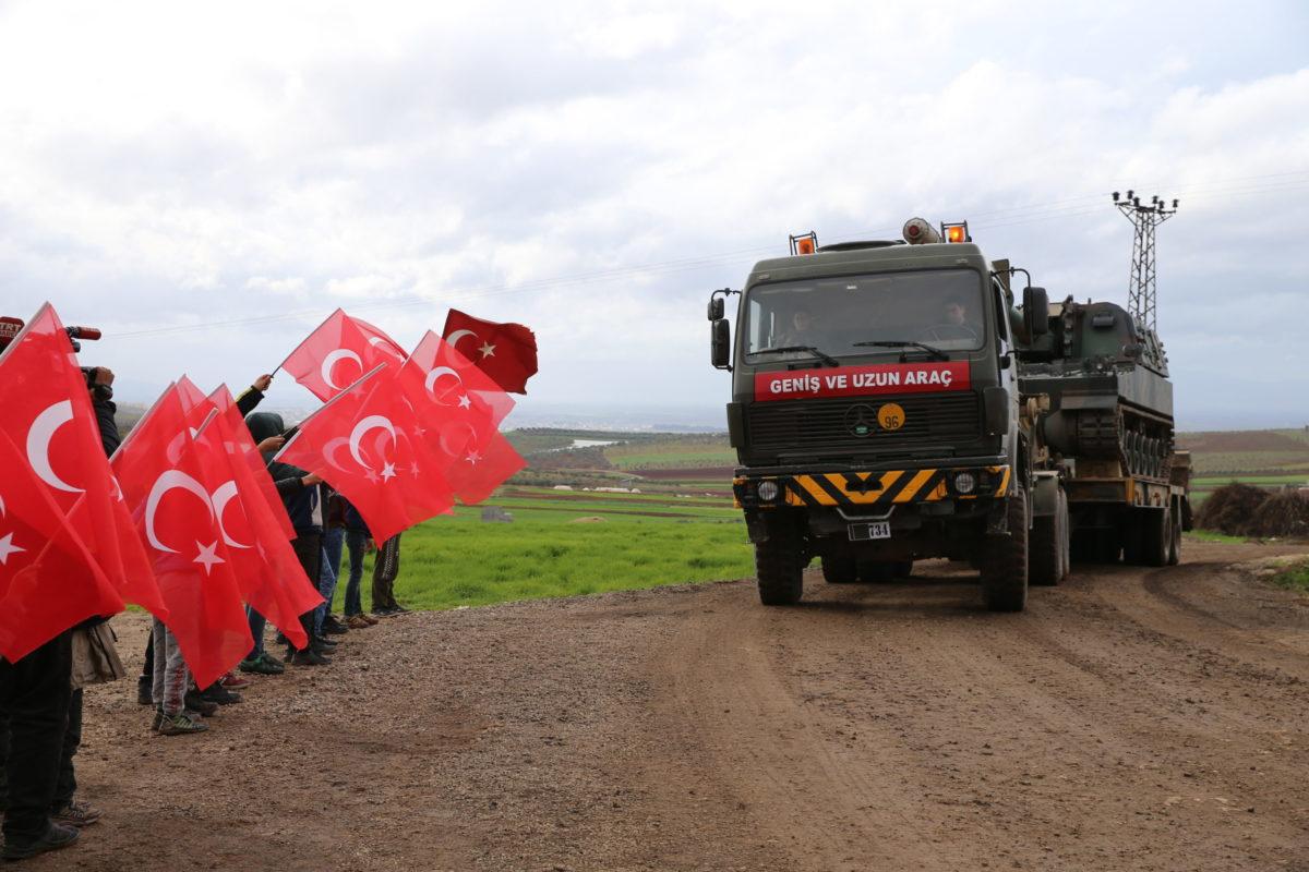 Deca iz provincije Hataj sa turskim zastavama pozdravljaju turski vojni konvoj na putu ka osmatračnicama u Idlibu, 07. februar 2020. (Foto: Cem Genco/Anadolu Agency)