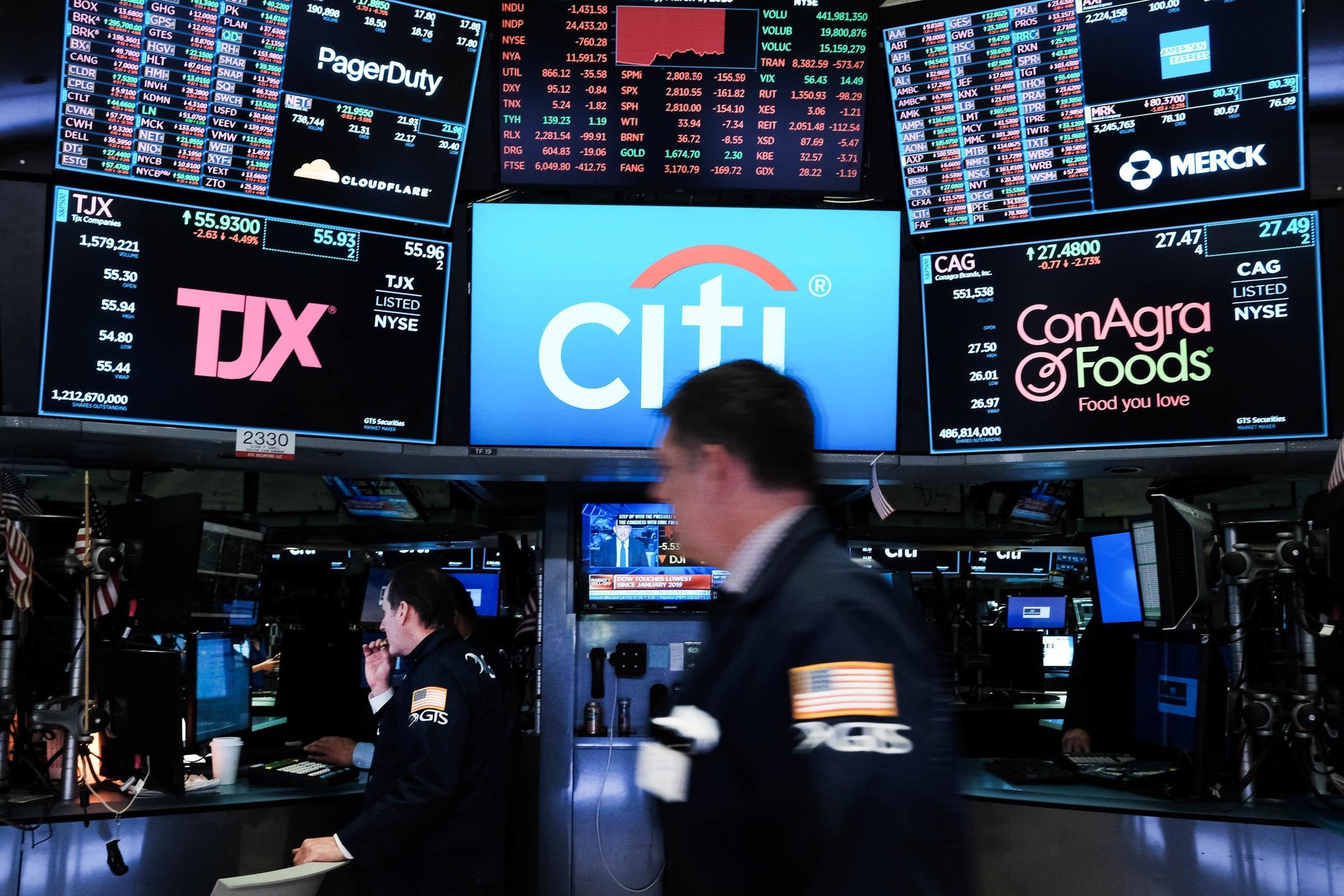 Radnik na Njujorškoj berzi prolazi pored ekrana na kojima su prikazane akcije kompanija (Foto: SPENCER PLATT/GETTY IMAGES)