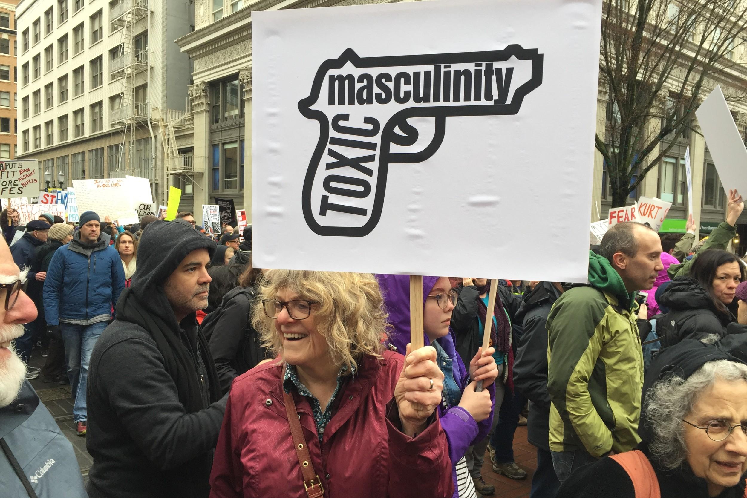 """Žena drži transparent na kome je """"toksična muževnost"""" prikazana u vidu pištolja, na protestu u Portlandu, 24. mart 2018. (Foto: Wikimedia/Sarahmirk)"""