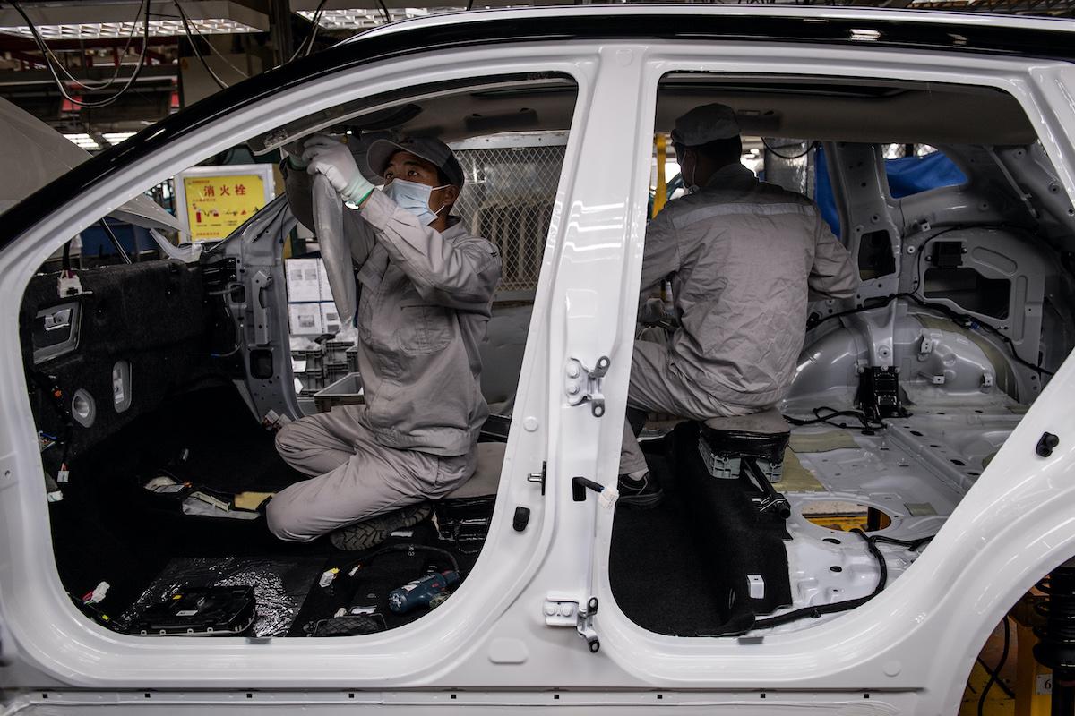 Kineski radnici sklapaju automobil u Hondinoj fabrici u Vuhanu, nakon epidemije koronavirusa, 23. mart 2020. (Foto: AFP)