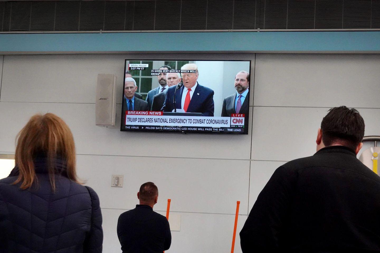 Putnici na aerodromu u Čikagu gledaju vesti u kojima predsednik Donald Tramp uvodi vandredno stanje u Sjedinjenim Državama (Foto: Scott Olson/Getty Images)