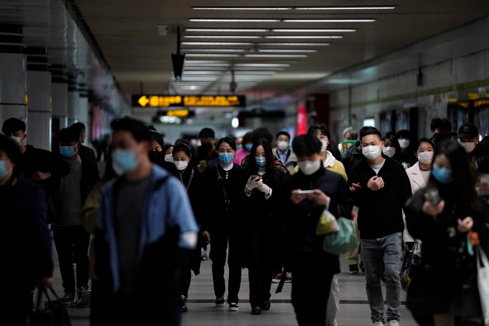 Prolaznici sa zaštitnim maskama na licu gledaju u telefone, na stanici podzemne železnice, Šangaj, 23. mart 2020. (Foto: REUTERS/Aly Song)