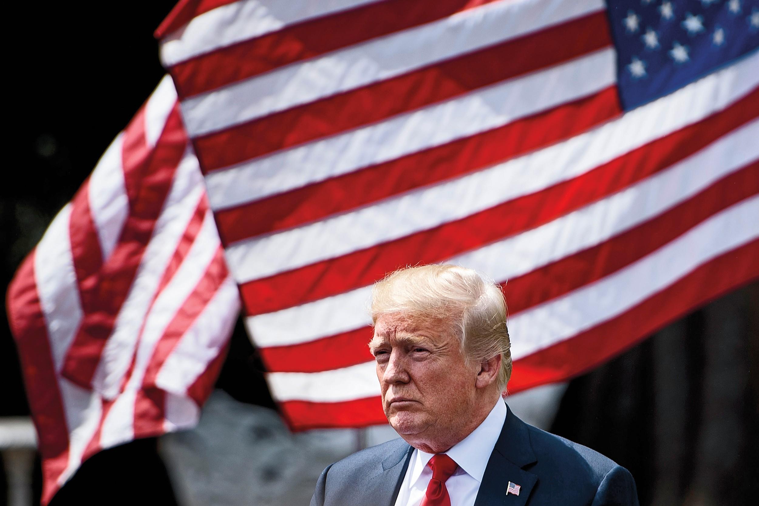 Zamišljeni Donald Tramp ispred američkih zastava (Foto: Brendan Smialowski/AFP/Getty Images)
