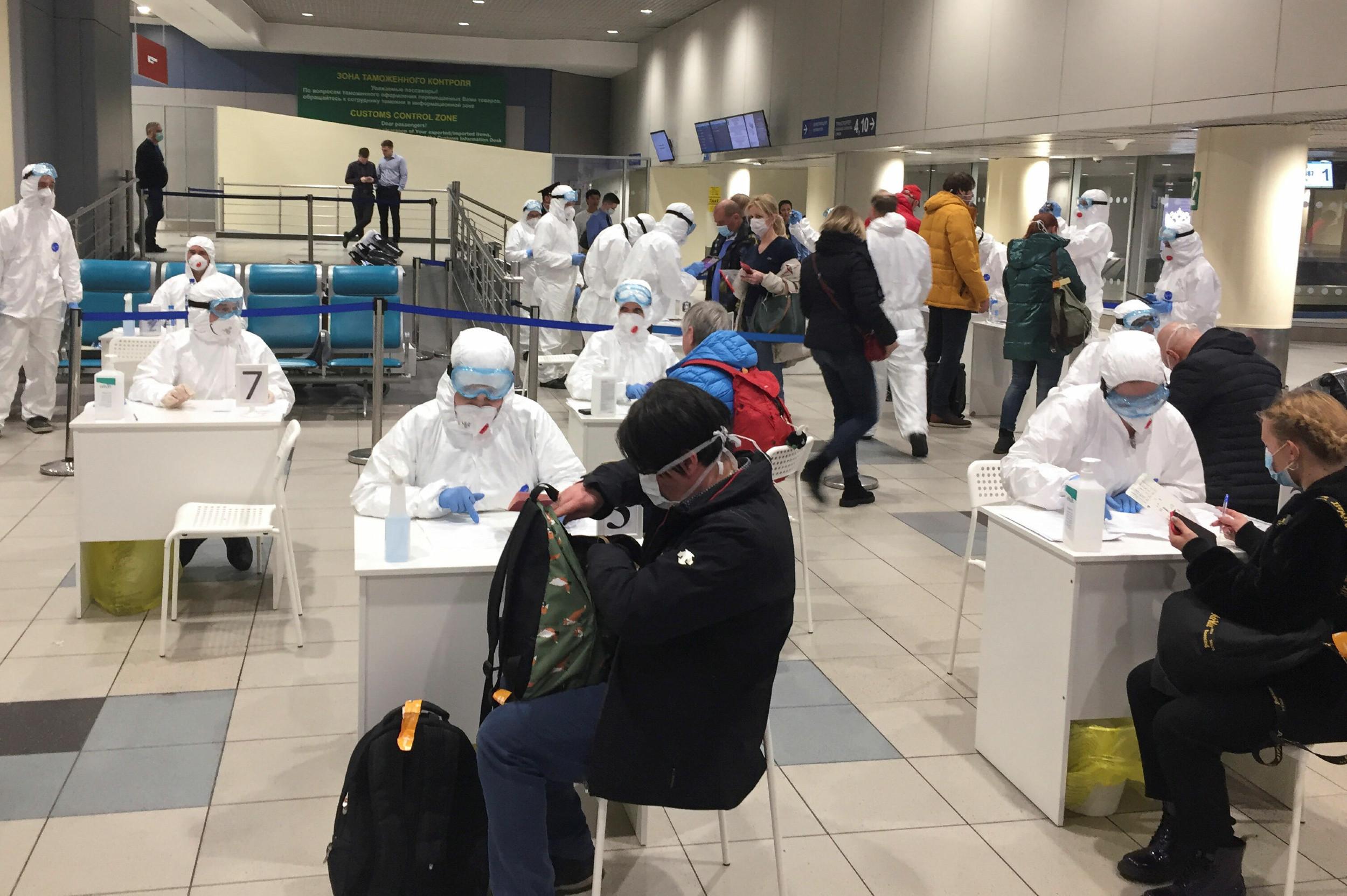 Ruski zvaničnici i medicinsko osoblje u zaštitnoj opremi proveravaju zdravstveno stanje putnika zbog virusa COVID-19 na moskovskom aerodromu Domodedovo, 07. mart 2020. (Foto: REUTERS/Stringer)