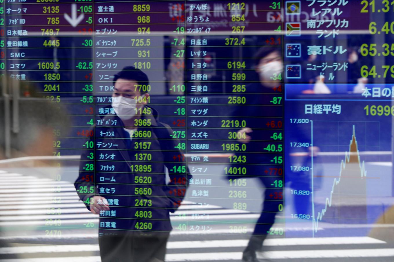 Pešak sa zaštitnom maskom gleda u ekran brokerske kuće u Tokiju na kom su prikazane cene akcija, 17. mart 2020. (Foto: Issei Kato/Reuters)