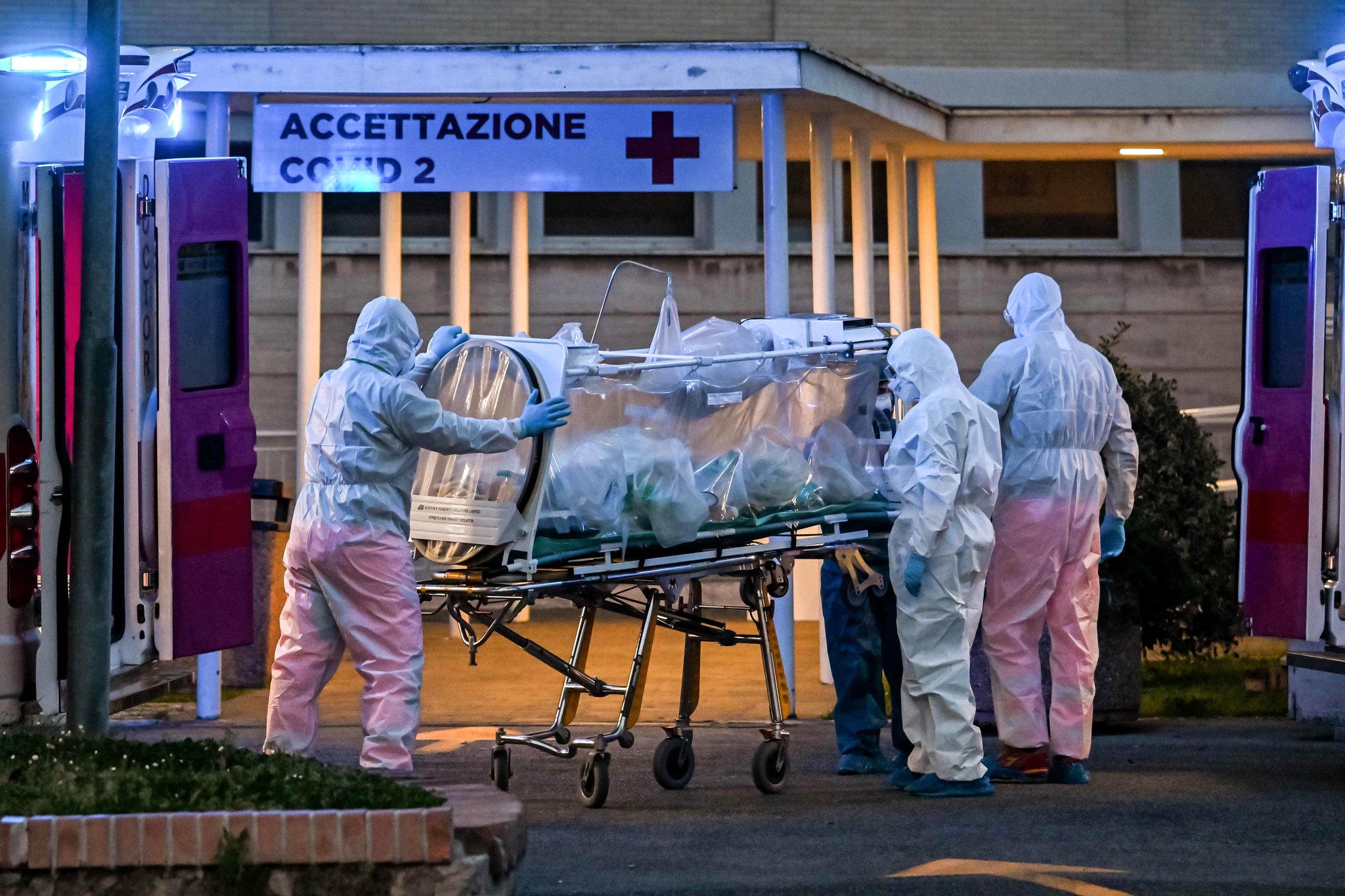 Medicinski radnici u zaštitnim odelima prevoze obolelog od koronavirusa u jednu od bolnica u Rimu (Foto: Andreas Solaro/Agence France-Presse/Getty Images)