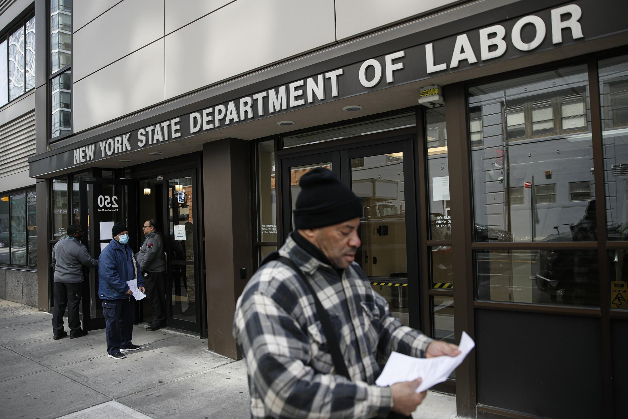 Građani Njujorka prolaze pored zgrade Ministarstva rada, 18. mart 2020. (Foto: AP Photo/John Minchillo)