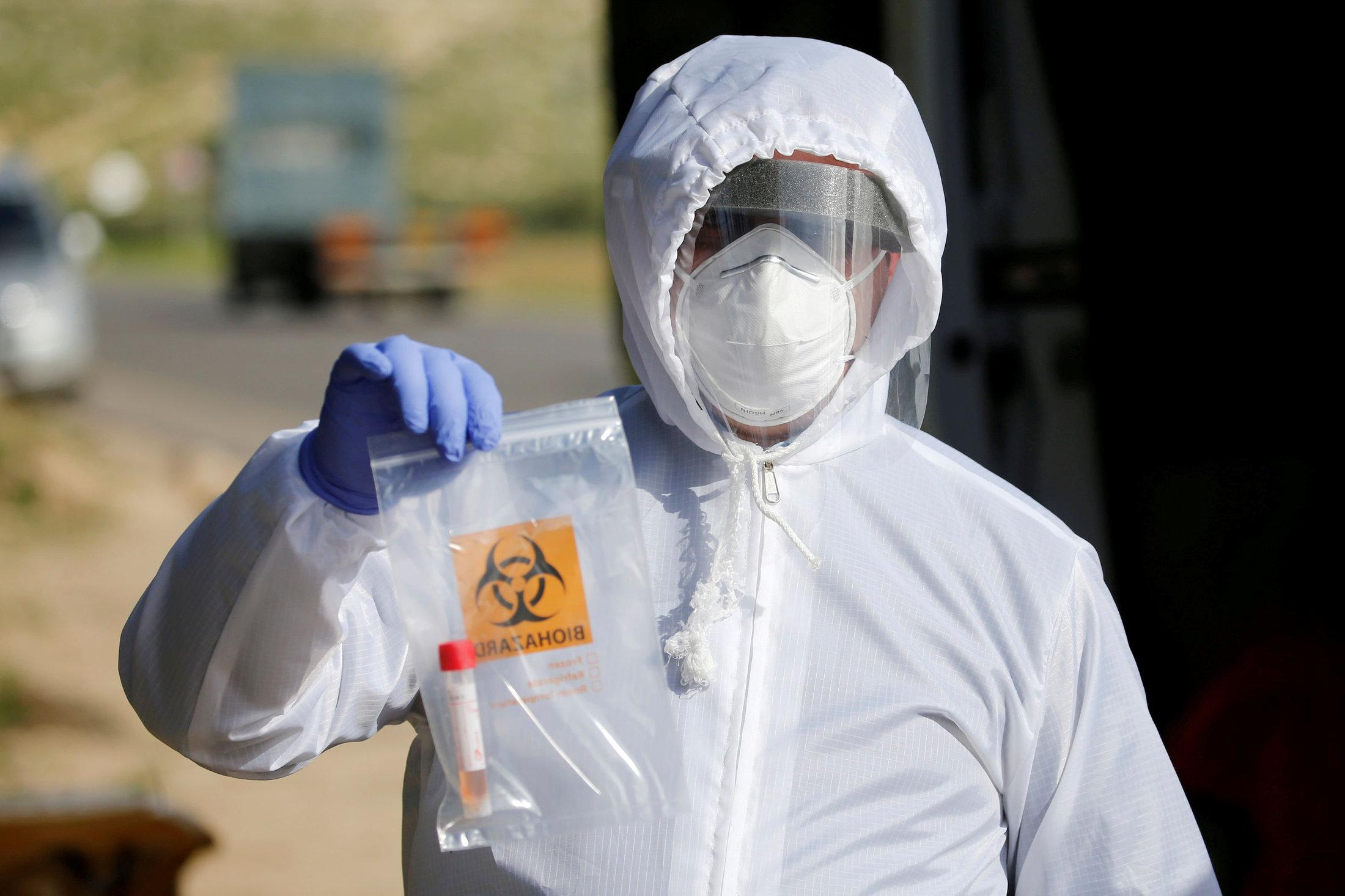 Medicinski radnik u zaštitnom odelu nosi uzorak nakon testiranja na COVID-19 (Foto: REUTERS/Mussa Qawasma)
