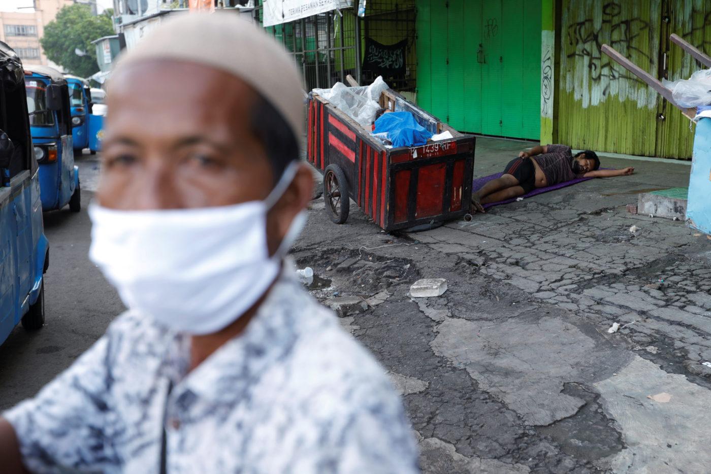 Ulični prodavac sa maskom na licu radi, dok u pozadini spavaju beskućnici, Džakarta, 31. mart 2020. (Foto: REUTERS/Willy Kurniawan)