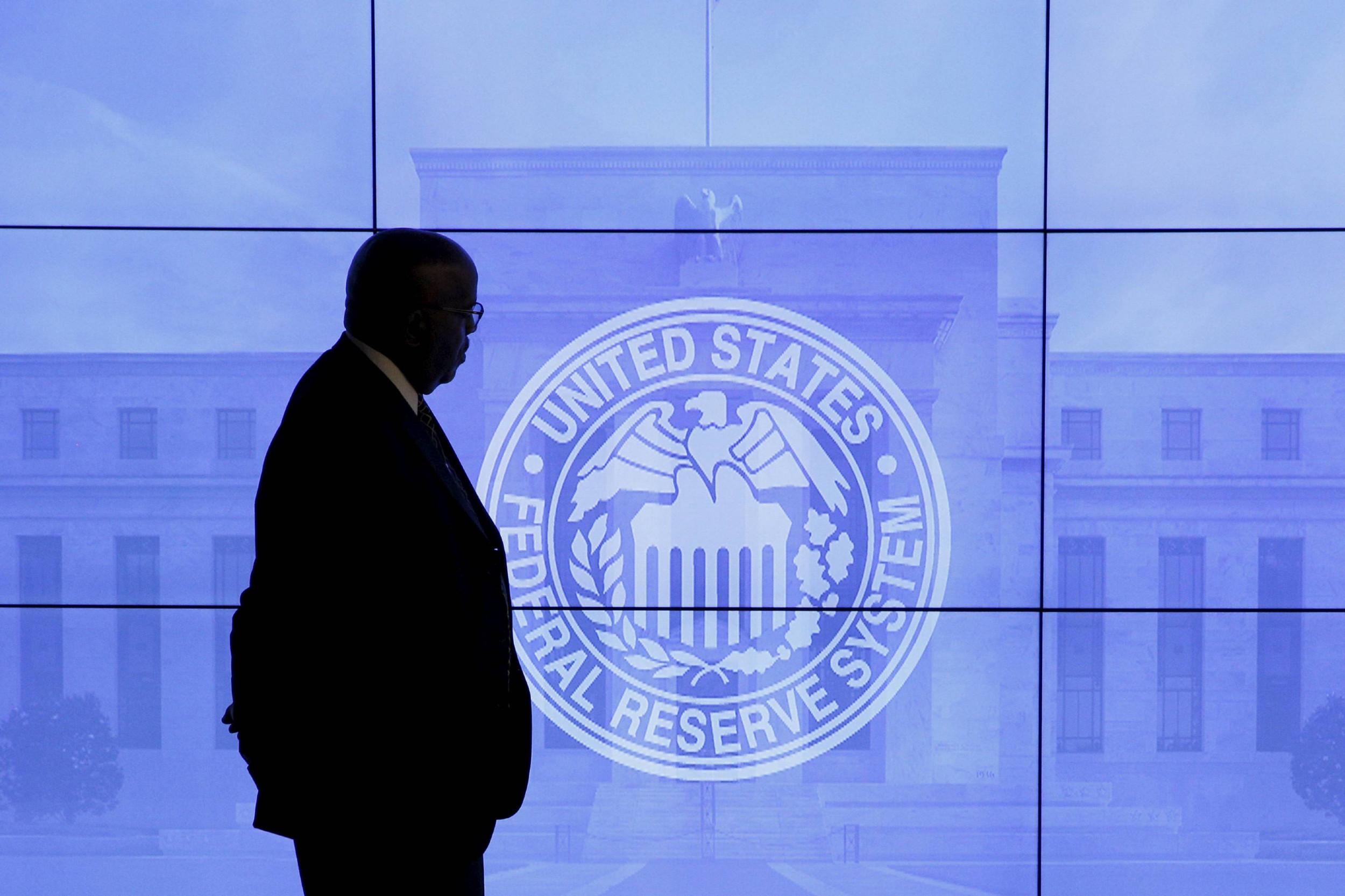 Čovek prolazi pored ekrana na kom se nalazi grb Federalnih rezervi (Foto: REUTERS/Kevin Lamarque)