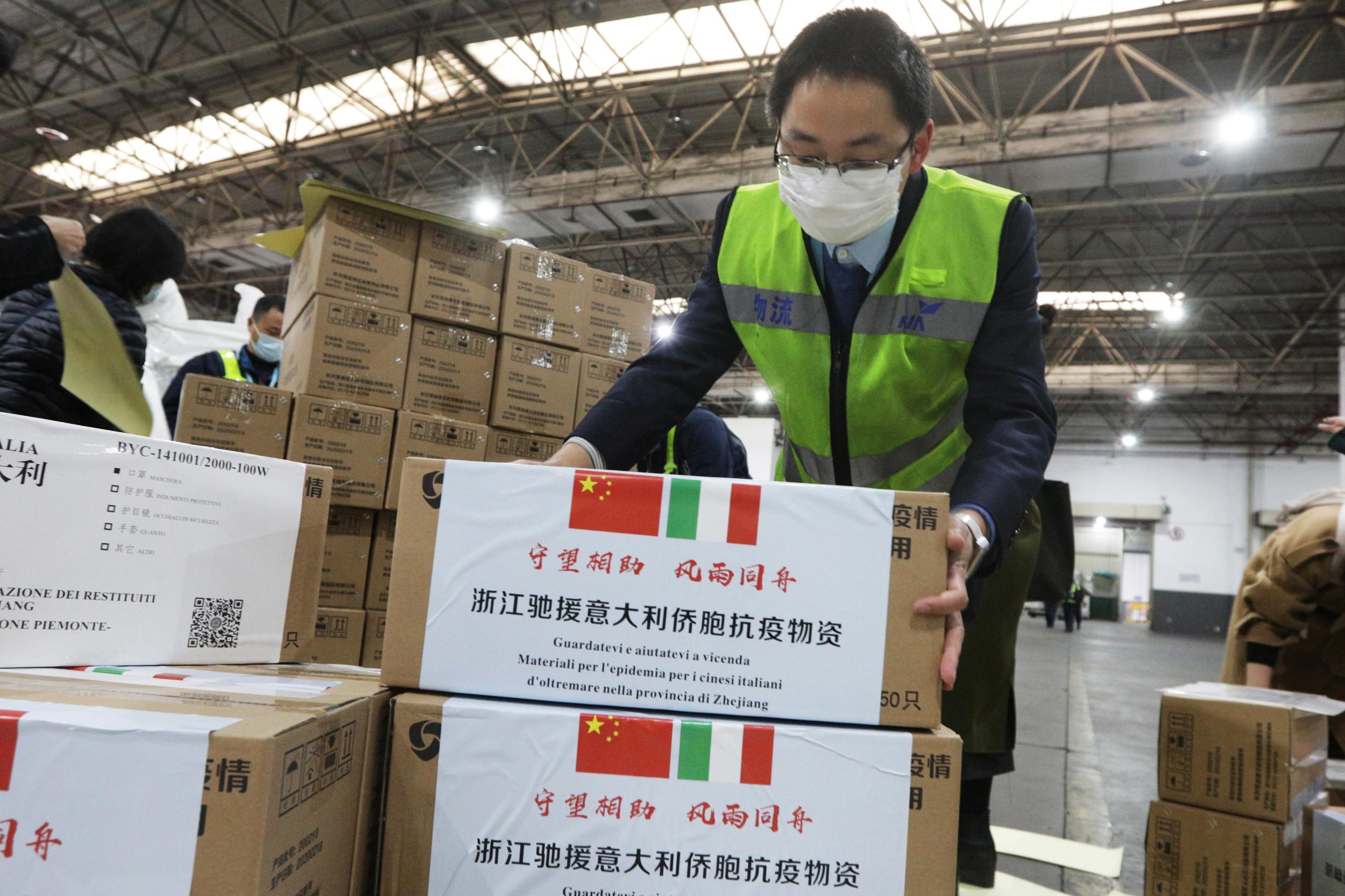 Radnik sa zaštitnom maskom slaže pakete medicinske pomoći koje Kina šalje Italiji u borbi protiv virusa COVID-19 (Foto: REUTERS)