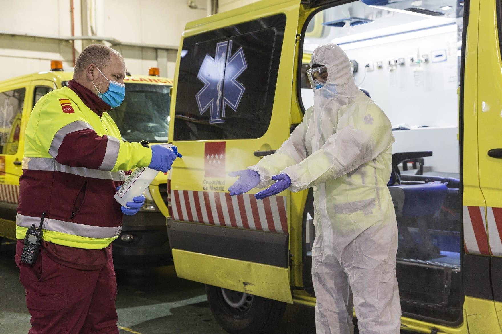 Pripadnik bolničkog obezbeđenja prska aspesolom ruke medicinskog radnika u zaštitnom odelu u Madridu (Foto: ferrovial.com)