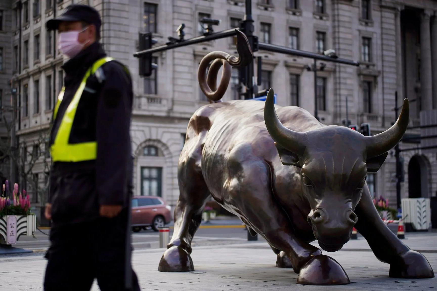 Čovek za zaštitnom maskom prolazi pored skulpture bika na Volstritu (Foto: ft.com)
