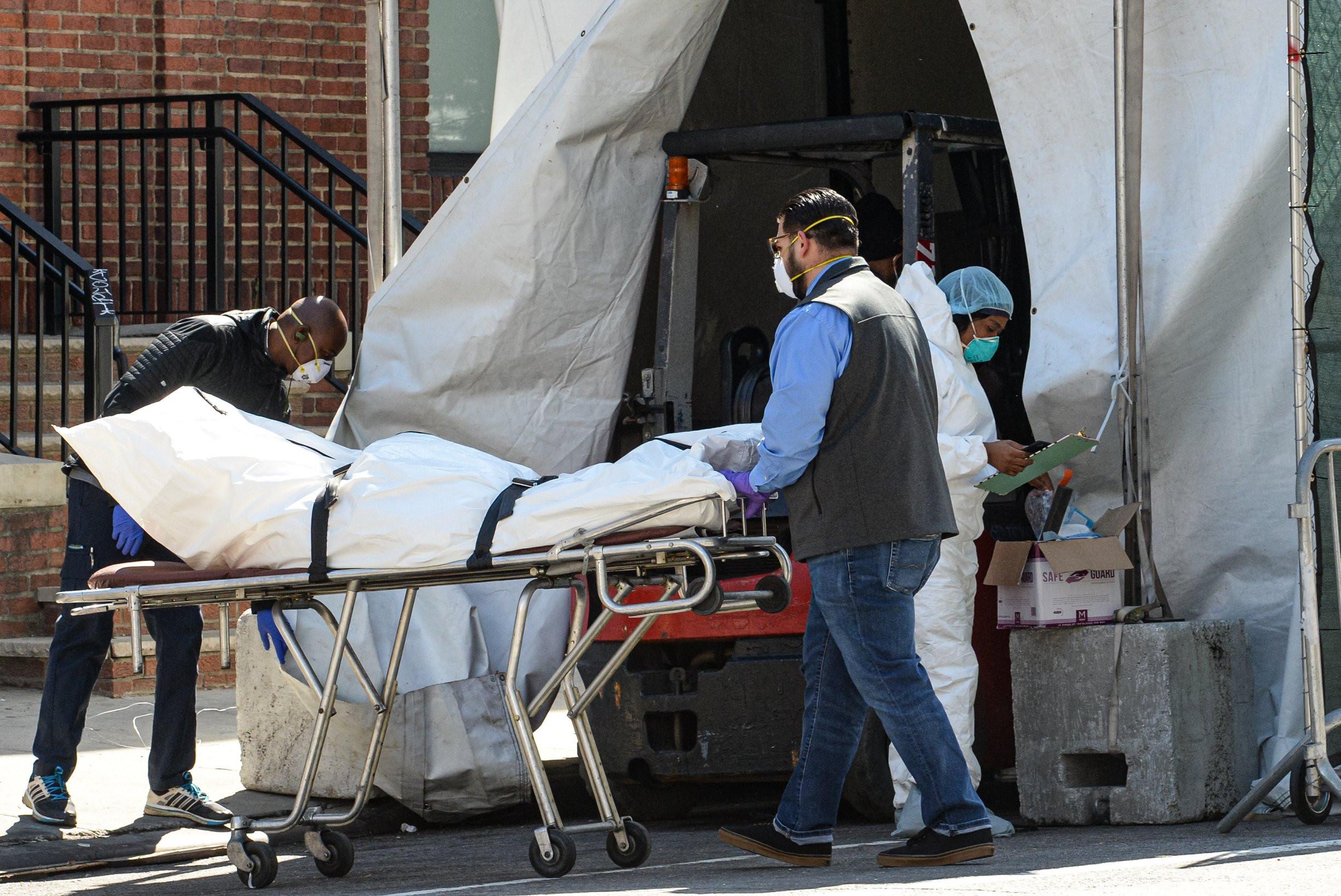 Medicinski radnici odvoze telo preminulog od virusa COVID-19 ispred Bruklin bolnice, Njujork, 06. april 2020. (Foto: Marcus Santos/ZUMA Wire)