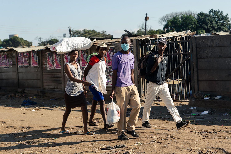 Ljudi prolaze pored zatvorene pijace u Harareu, 30. mart 2020. (Foto: Jekesai Njikizana/AFP/Getty Images)