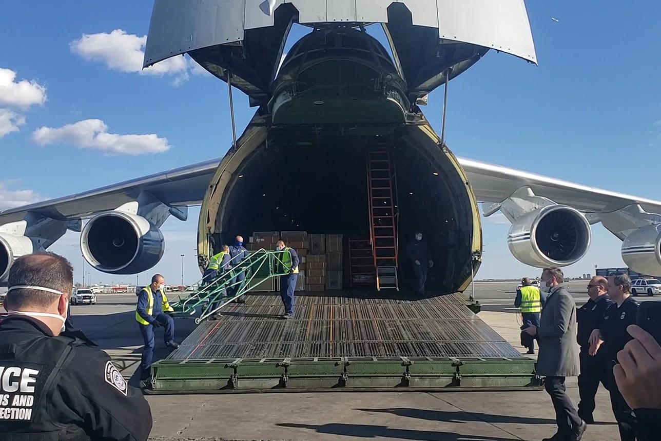 """Radnici istovaruju pakete humanitarne pomoći iz ruskog aviona na aerodromu """"Džon F. Kenedi"""" u Njujorku, 01. april 2020. (Foto: TASS)"""