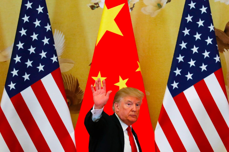 Амерички председник Доналд Трамп пролази поред америчке и кинеске заставе (Фото: Andy Wong/AP Images)