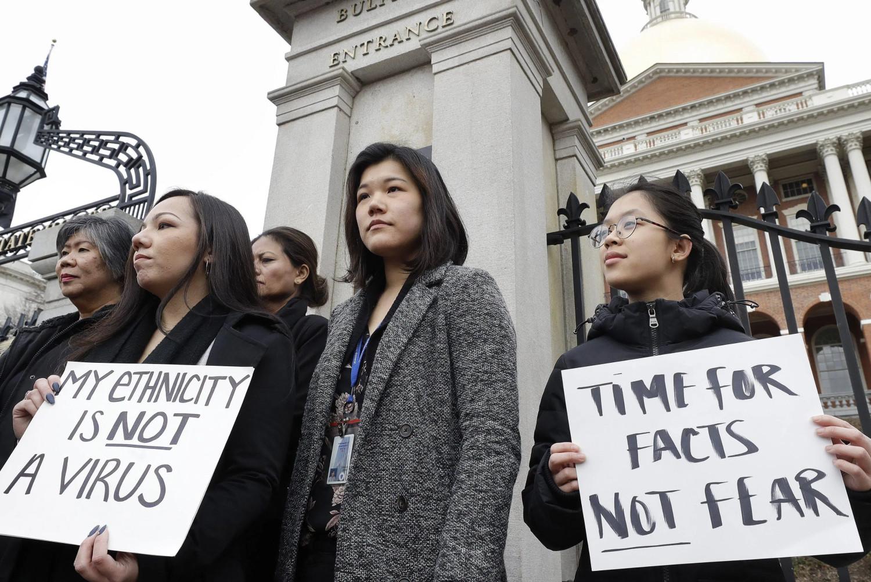 """Кинески грађани у Бостону протестују због наратива о кинеској кривици за коронавирус носећи транспаренте са називима """"Моја националност није вирус"""" и """"Време је за чињенице, а не страх"""" (Фото: AP Photo/Steven Senne)"""