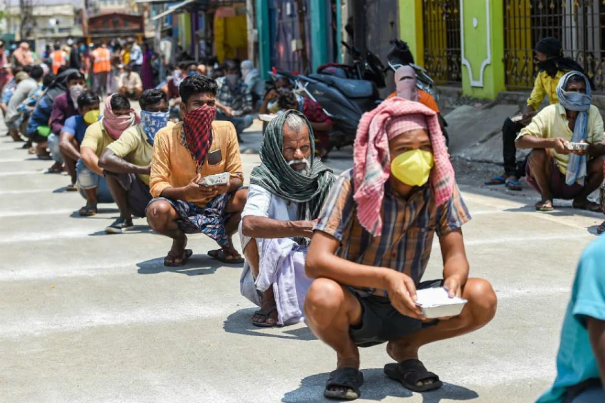 Radnici u Indiji održavaju socijalnu distancu dok čekaju u redu za pakete hrane zbog pandemije virusa COVID-19 (Foto: PTI Photo)
