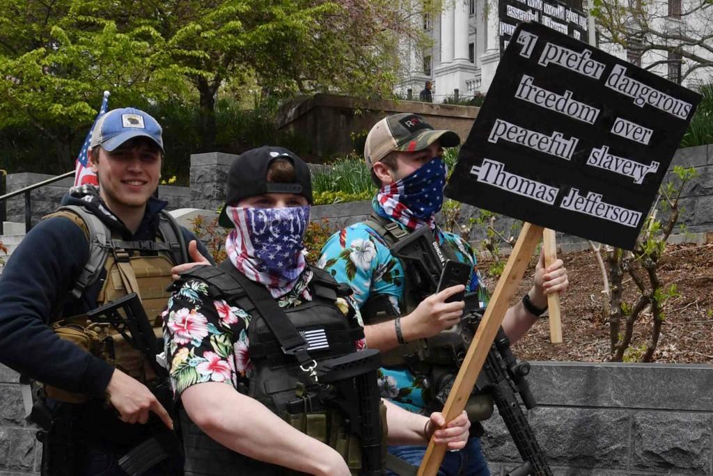 "Наоружани протестанти са транспарентом на коме је наведен цитат Томаса Џеферсона ""Више волим опасну слободу него мирно ропство"" (Фото: Nicholas Kamm/AFP via Getty Images)"