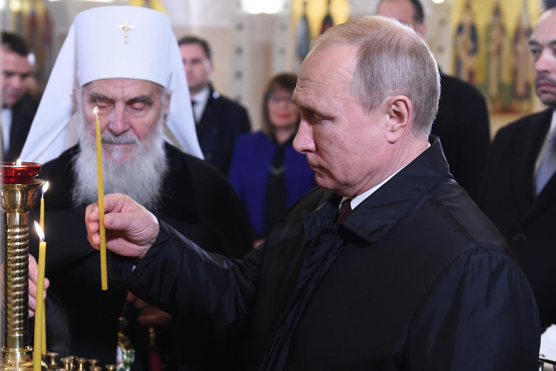 Predsednik Rusije Vladimir Putin pali sveću u prisustvu patrijarha Irineja u Kripti Hrama Svetog Save tokom posete Beogradu, 17. januar 2019. (Foto: Ministarstvo odbrane RS)