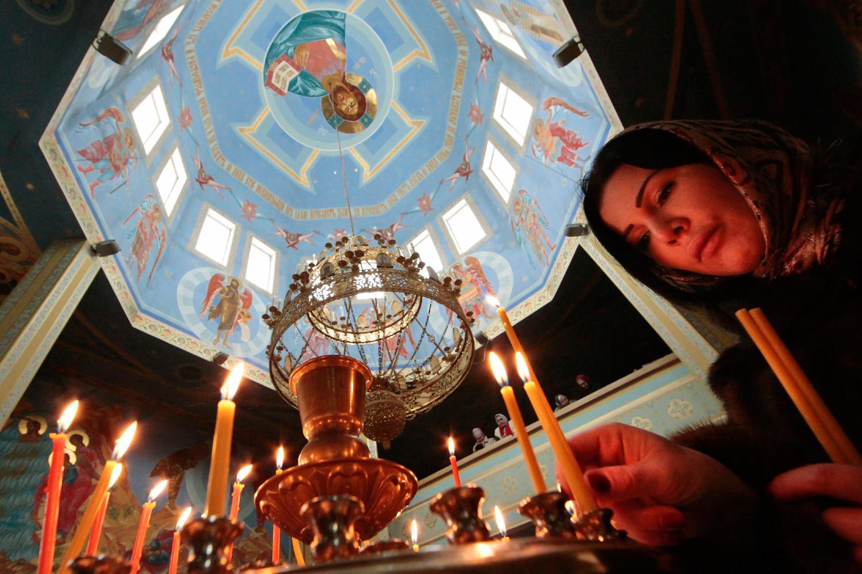 Vernica pali sveću u hramu Ruske pravoslavne crkve (Foto: AP)