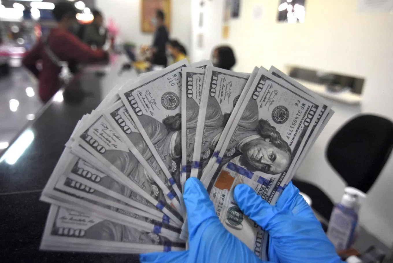 Радник у мењачници разврстава америчке доларе приликом замене валута (Фото: Antara/Indrianto Eko Suwarso)