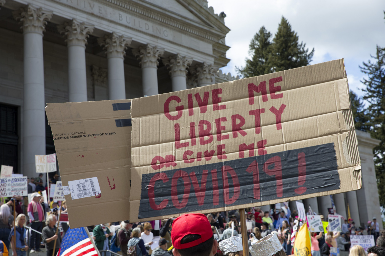"""Građani tokom protesta protiv kućnog karantina ispred Kapitola drže transparent na kome piše """"Dajte mi slobodu ili mi dajte COVID-19"""", Vašington, 19. april 2020. (Foto: Karen Ducey/Getty Images)"""
