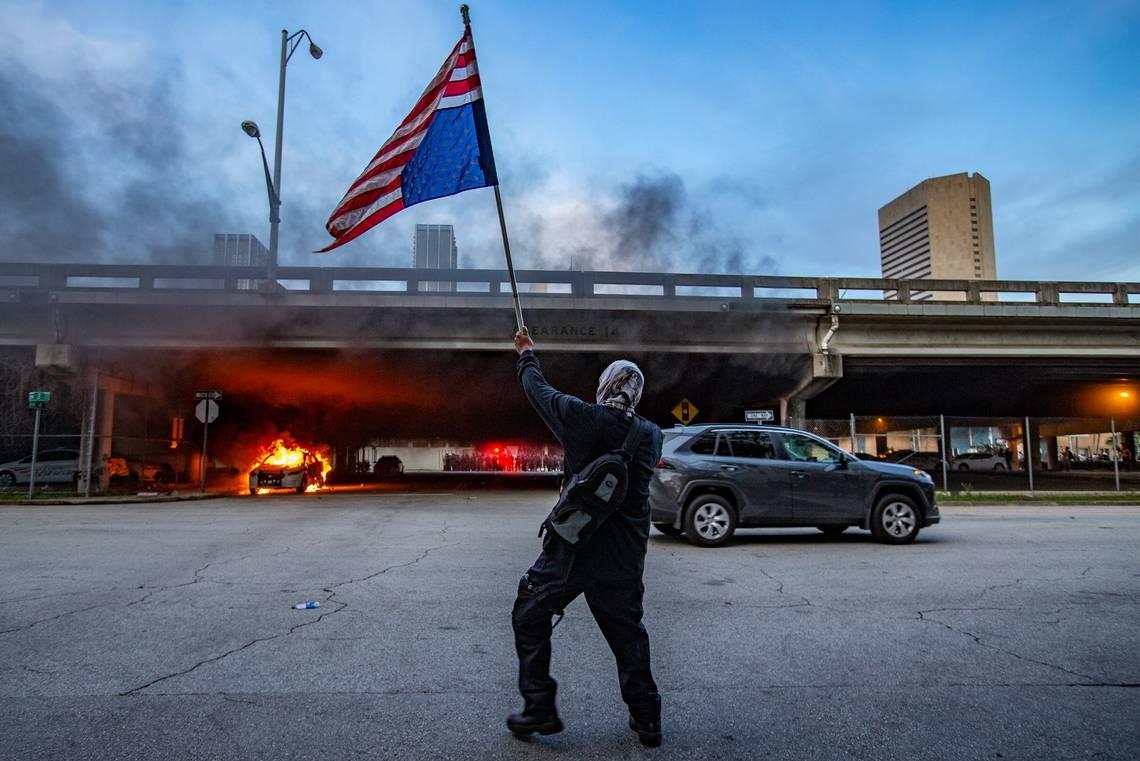 Demonstrant maše američkom zastavom okrenutom naopačke ispred zapaljenih automobila tokom protesta zbog ubistva Džordža Flojda, Majami, 30. maj 2020. (Foto: Al Diaz Adiaz/Miami Herald)
