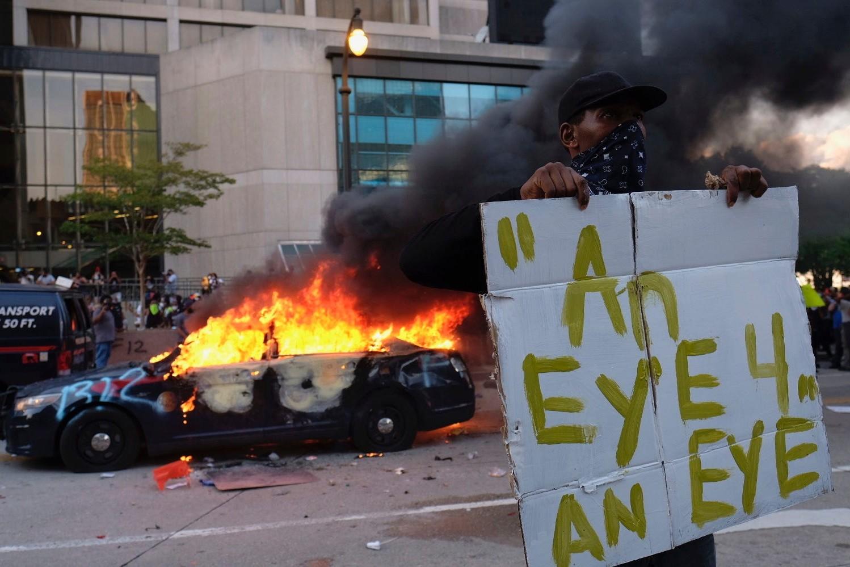 """Demonstrant drži transparent na kome piše """"Oko za oko"""" ispred zapaljenog policijskog automobila na protestu zbog ubistva Džordža Flojda u Atlanti (Foto: newsplus24.com)"""