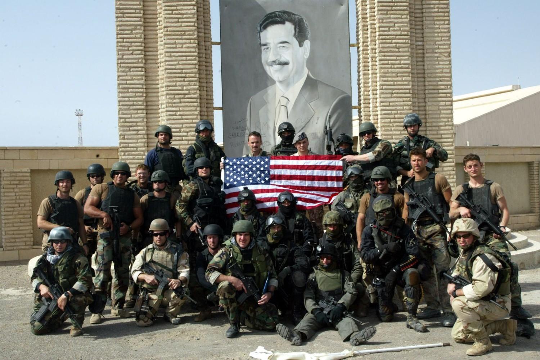 Poljski specijalci i pripadnici američke mornarice sa američkom zastavom poziraju ispred slike iračkog predsednika Sadama Huseina u luci Um Kasr na jugu Iraka, 23. mart 2003. (Foto: Reuters/Desmond Boylan)