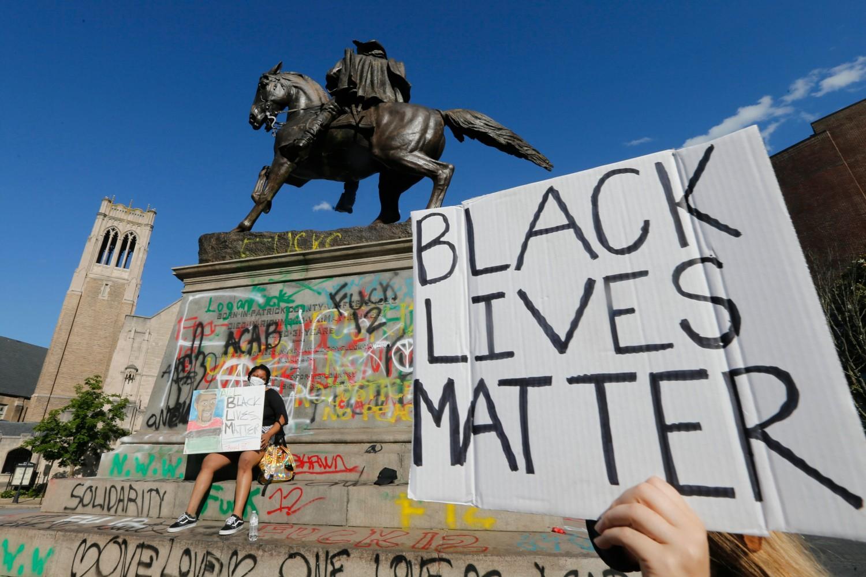 """Demonstrant drži transparent na kome piše """"Crni životi su važni"""" ispred vandalizovanog spomenika generalu Konfederacije Džebu Stjuartu, Ričmond, Virdžinija, 31. maj 2020. (Foto: AP Photo/Steve Helber)"""