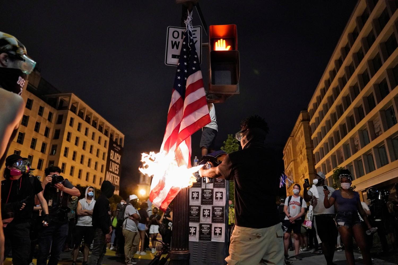 Demonstrant spaljuje američku zastavu tokom protesta zbog ubistva Džordža Flojda u blizini Bele kuće, Vašington, 23. jun 2020. (Foto: REUTERS/Erin Scott)